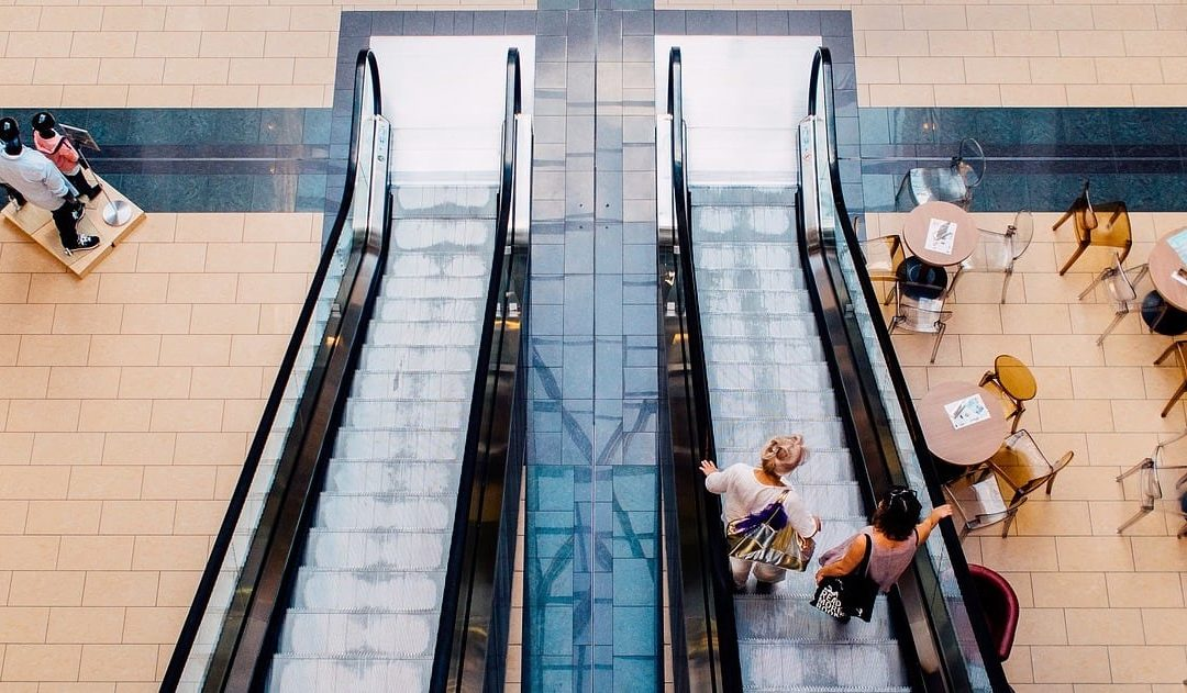 two females travelling down an escalator in a shopping mall