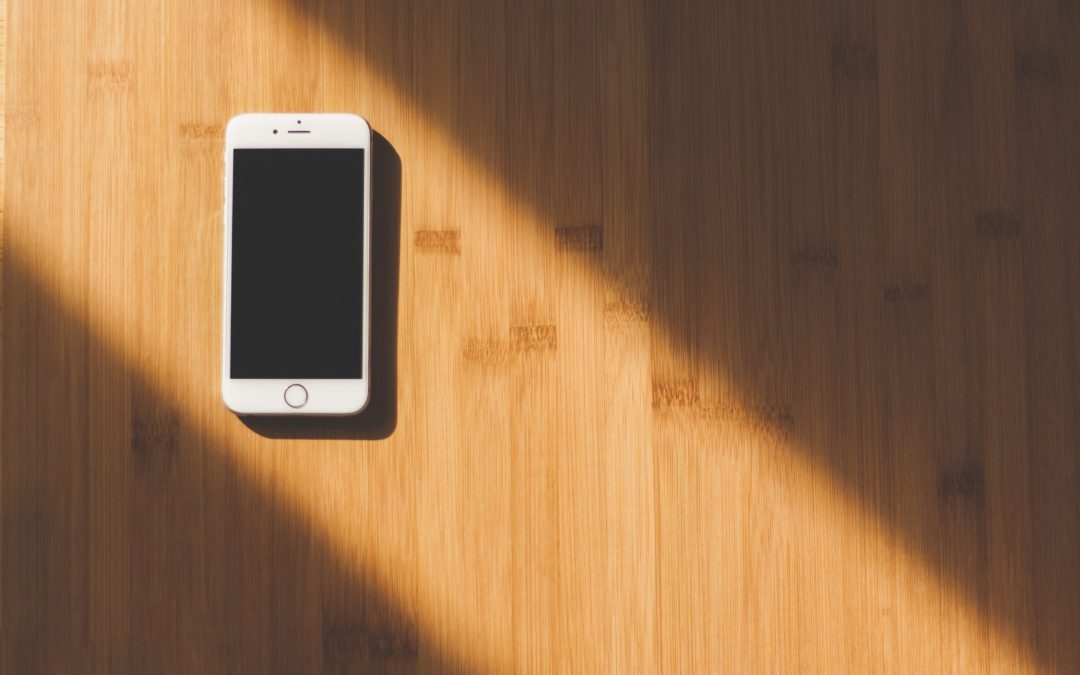 white iphone on a wooden table